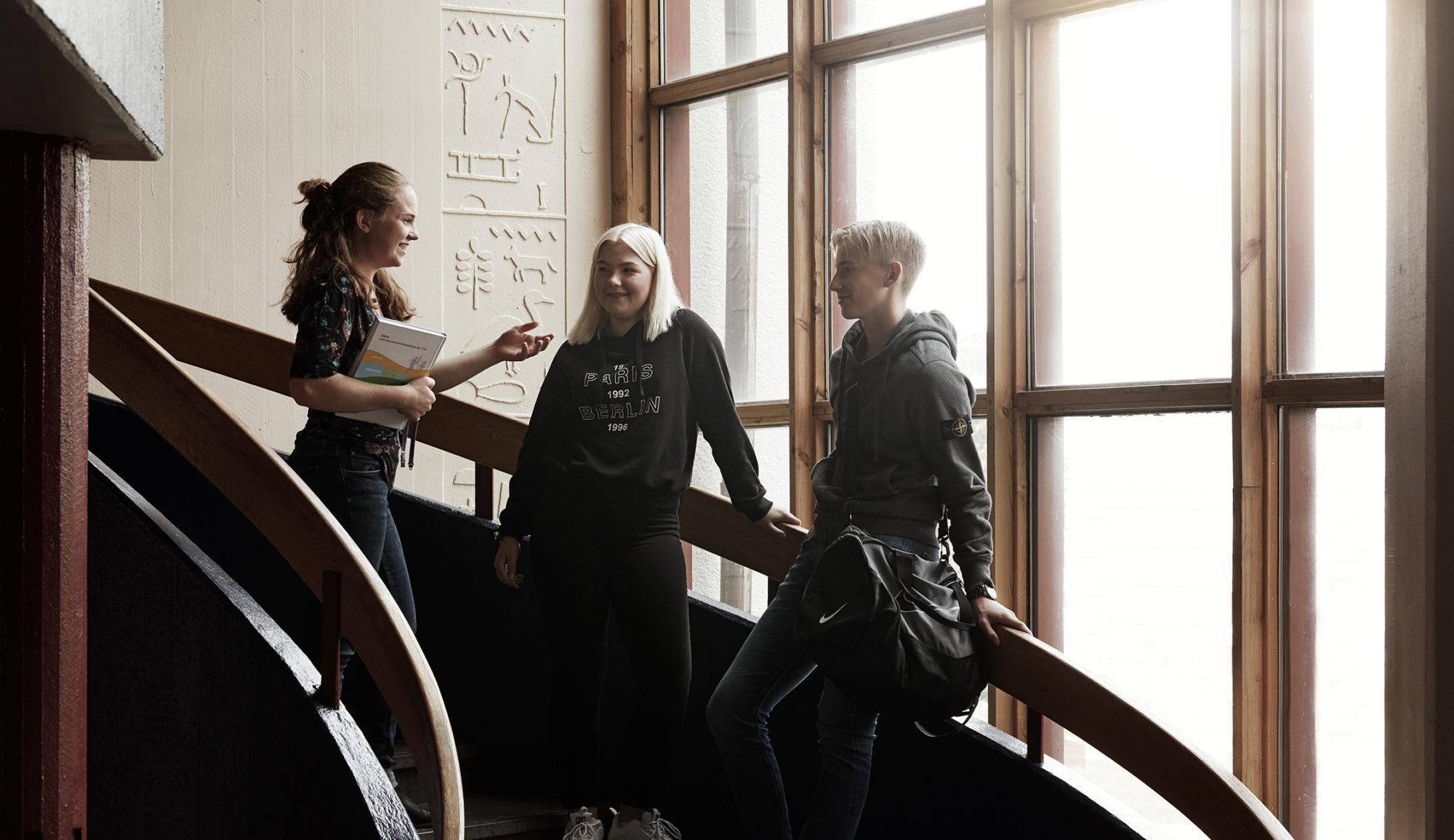 Tre elever pratar i skolan på trappa