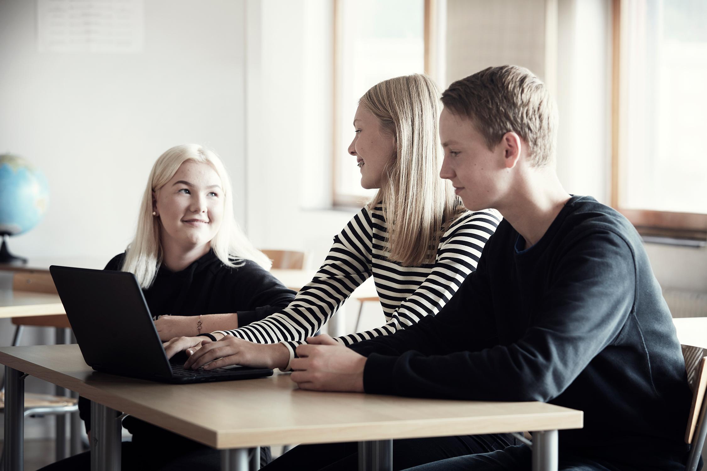 Tre elever sitter vid skolbänken